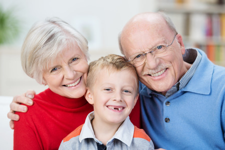 Beautiful family portrait showing the generations with a cute little boy with his front teeth missing sitting with his happy smiling grandparents in a close embrace
