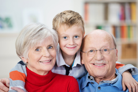 Proud happy elderly grandparents posing with their adorable little grandson hugging them from behind grinning playfully at the camera
