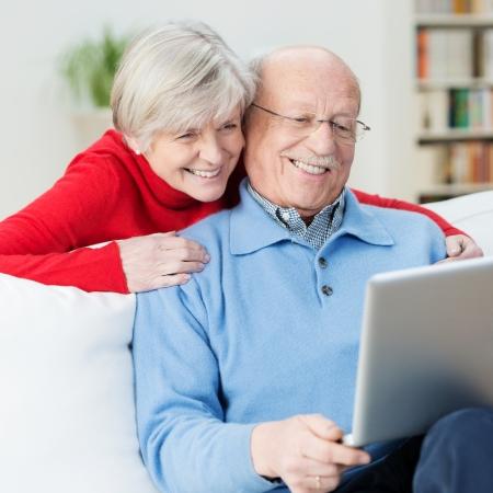 年配のカップルとして彼らの妻よりよい一見のために彼女の夫の肩の上に傾いたと画面に何かを見て笑っているラップトップ コンピューターを使用