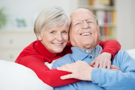 devoted: Devoted happy senior couple sitting in a close embrace on a sofa in the living room relaxing and laughing