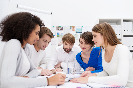 entrepreneurs: Dedicated young multiethnic business team in a meeting sitting grouped around a table in the office holding a serious discussion as they analyse paperwork