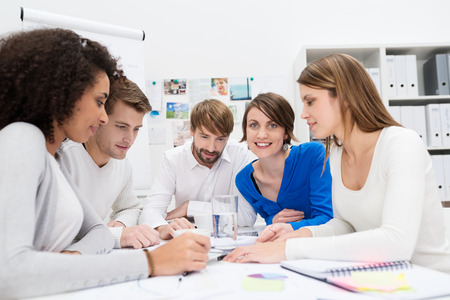 Dedicated young business team in a meeting sitting grouped around a table in the office holding a serious discussion