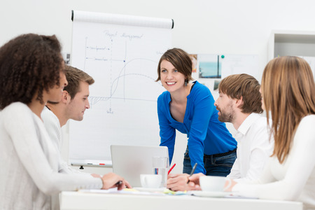 Businesswoman giving a presentation to her team as she stands in front of a flip chart and laptop computer smiling as she answers questions photo