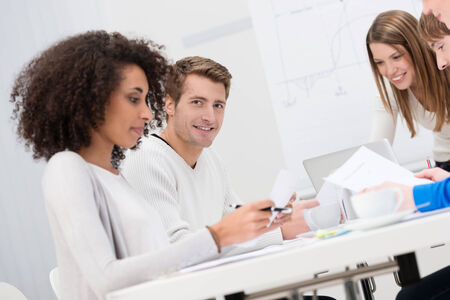 Group of business colleagues in a meeting sitting at a table discussing paperwork with focus to a smiling handsome young man at the back photo