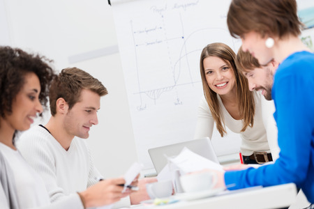 sit around: Female team leader with her business team conducting a brainstorming and strategy planning meeting as they sit around a table in the office, focus to her smiling face