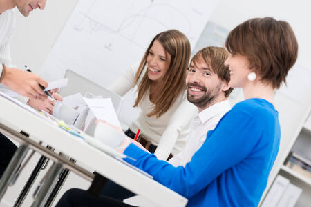 Young businessman with his female coworkers sitting at a table together having a meeting and discussion, focus to his face with a lovely friendly smile photo
