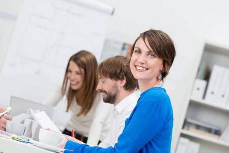 Smiling confident friendly businesswoman sitting in a meeting with her colleagues turning to smile at the camera photo
