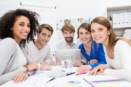Aantrekkelijke gemotiveerde jonge multi-etnische business team zitten rond een tafel in het kantoor met een vergadering met de teamleider