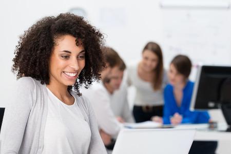 Vrij Afrikaanse Amerikaanse zakenvrouw het lezen van informatie op haar laptop computer