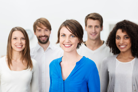 group of young adults: Happy manageress with her business team grouped around her as they look at the camera with friendly smiles