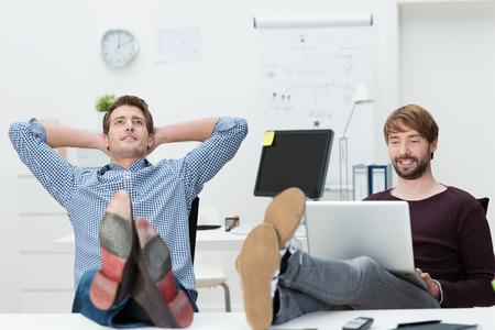 2 つのリラックスした自信を持って若いビジネス パートナーの机の上と満足の笑顔自分の足で座って自分の成功を確信