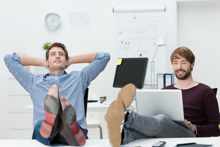 reclining chair: Two relaxed confident young business partners sure of their own success sitting with their feet up on the desk and complacent smiles Stock Photo