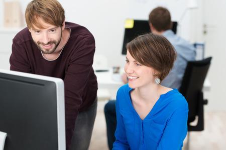 ufficio aziendale: Colleghe sorridente nella soddisfazione che lavorano insieme su un computer desktop consultando le informazioni sul monitor di un progetto condiviso Archivio Fotografico