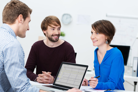 Young business team with an attractive woman and two men sitting around a desk and laptop computer having a brainstorming session photo