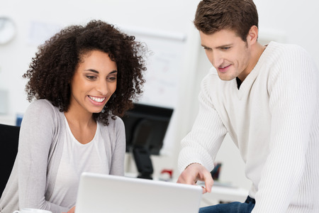 Dedicated business partners having a meeting sitting at a table in the office with an attractive young African American woman sharing information with a handsome male colleague Stock Photo