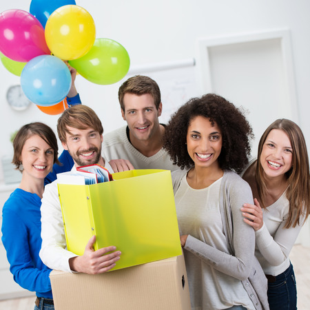 office party: Successful motivated young business team celebrating as they move to new office premises to begin a new business venture with their cardboard boxes and party balloons Stock Photo