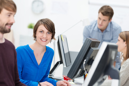 Happy motivated attractive young businesswoman sitting at her desk in a busy office giving the camera a bright friendly smile