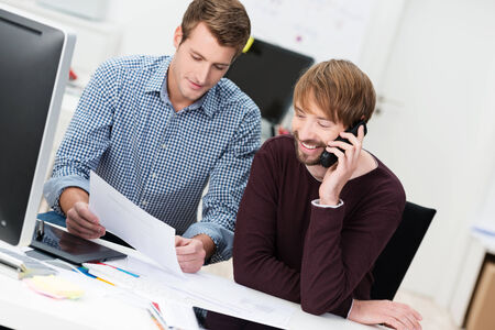 chats: Two male business partners working in the office sitting at a desk discussing a document while one man chats on his mobile phone