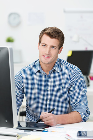 shirtsleeves: Handsome young businessman in shirtsleeves sitting working at his desktop computer using a tablet and stylus to navigate Stock Photo