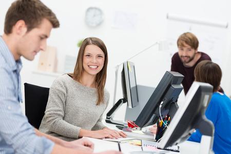 Lachende jonge zakenvrouw in een druk kantoor zit aan haar bureau op haar computer, omringd door hardwerkende collega's