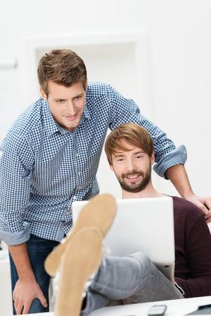 pies masculinos: Dos socios de negocios ocasionales que trabajan en la oficina, uno con los pies sobre el escritorio con un ordenador vigilado por su colega que se inclina sobre él
