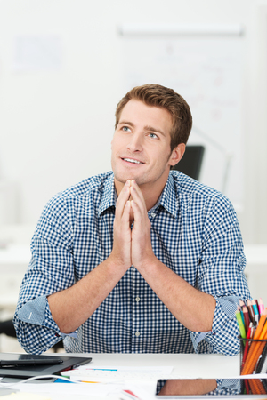 Handsome happy young businessman sitting daydreaming at his desk with a contented smile on his face photo
