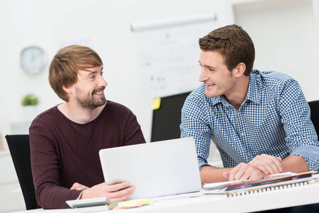 business consulting: Two male friends working together in the office sitting smiling and chatting as they share a laptop computer