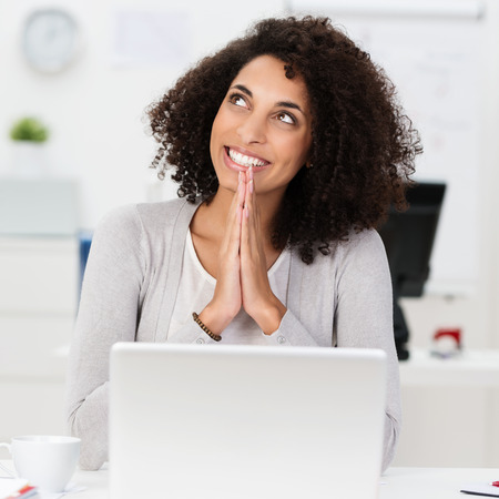 vivacious: Beautiful vivacious smiling African American businesswoman offering a prayer of thanks at her desk for a successful business outcome Stock Photo
