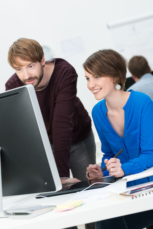 it tech: Attractive male and female co-workers working in cooperation at the office Stock Photo
