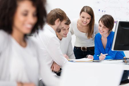 recursos humanos: Grupo multiétnico diverso de jóvenes empresarios en una reunión sentado en una mesa en la oficina de discutir su estrategia de negocio y el intercambio de información Foto de archivo