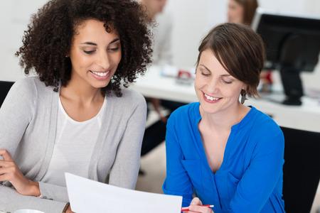amigas conversando: Dos sonrientes mujeres de negocios que trabajan en un documento mientras se sientan juntos en un escritorio en la oficina, una es afroamericana