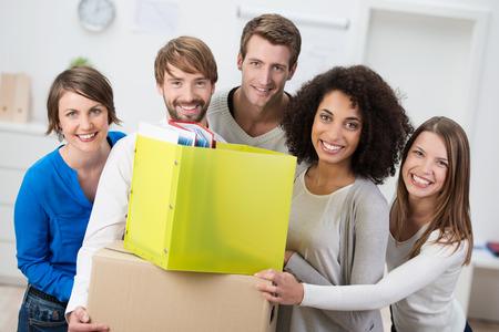 ufficio aziendale: Felice giovane gruppo multietnico di amici trasferirsi in nuovi alloggi in piedi, raggruppati intorno scatole di cartone contenenti file di lavoro e oggetti personali, o di una squadra di affari di iniziare un nuovo partenariato