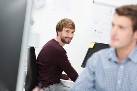 View past a hardworking male colleague with focus to a smiling friendly businessman at the office photo