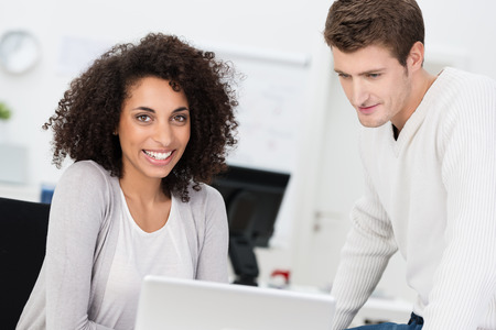 Beautiful African American businesswoman with a frizzy afro hairstyle smiling at the camera as she works alongside a male colleague Stock Photo