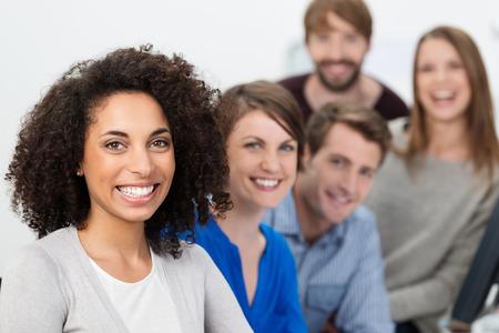 people  camera: Equipo multi�tnico entusiasta �xito empresarial liderado por una hermosa joven empresaria afroamericana posando juntos en una fila con el foco en la mujer
