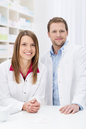 Successful pharmacy partnership with a confident young male and female pharmacist standing close together behind the counter in the pharmacy smiling at the camera photo