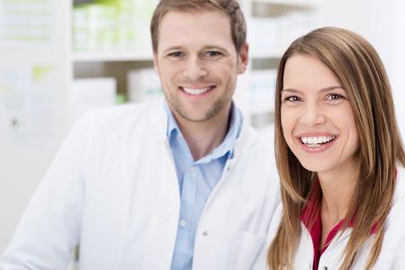 カメラで幸せそうに笑って幸せな若い男性と女性薬剤師と薬局でチームワークを自分の顔のクローズ アップ 写真素材