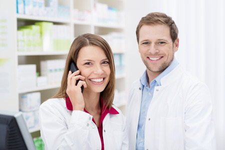 shop skill: Smiling attractive female pharmacist chatting on the phone watched by a handsome male colleague as they stand in the pharmacy Stock Photo