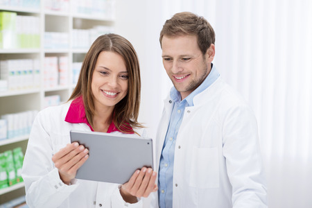 Two smiling young pharmacists, one male and one female, stand side by side in the pharmacy checking information on a tablet computer