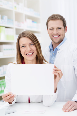 advertising woman: Beautiful pharmacist displaying a blank white sign as she stands behind the counter in the pharmacy with a male colleague Stock Photo