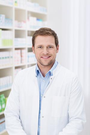 Lachende knappe mannelijke apotheker staan in de apotheek in zijn witte jas Stockfoto