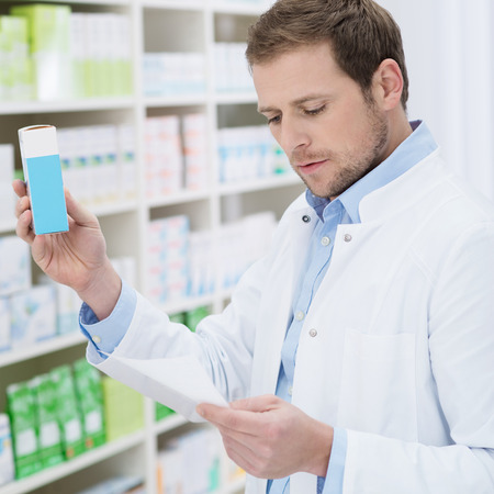 Pharmacist fulfilling a prescription holding medication in his hand as he checks the script