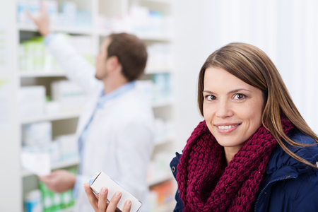 Smiling beautiful woman waiting in a pharmacy for the pharmacist to fulfill her prescription holding a box of medication in her hand photo