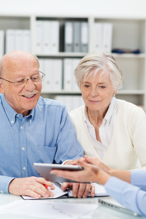 Senor couple in a business presentation leaning forwards to look at information on a tablet computer held out by their business broker photo