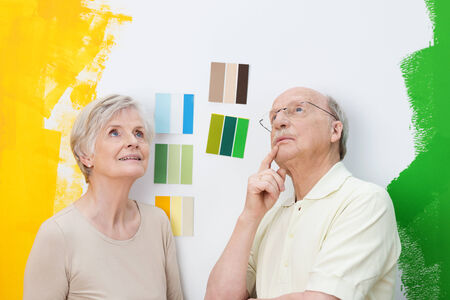 deciding: Happy elderly couple renovating their home standing looking at colour swatches on a wall trying to make a decision having already tried green and yellow