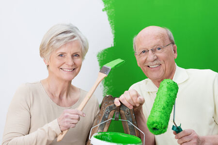 Elderly couple renovating their house painting the wall a vivid shade of green as they hold up the can of paint and their roller and brush photo