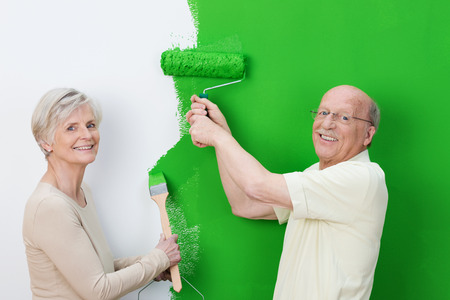 Pleased senior couple showing off the new wall colour as they paint the house interior a shade of vivid green photo