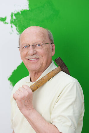 capable: Capable elderly man doing home renovations standing with a hammer over his shoulder in front of a half painted green and white wall Stock Photo