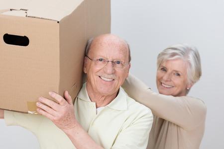 persona de la tercera edad: Feliz pareja senior de trabajo en equipo a medida que avanzan casa prestarse asistencia mutua para llevar a una gran caja de cart�n marr�n