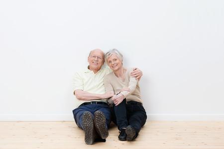 Loving älteres Ehepaar in ihrem neuen Zuhause sitzen nebeneinander auf dem nackten Holzboden lächelnd in Genugtuung, ihr Ziel erreicht, ein Traumhaus